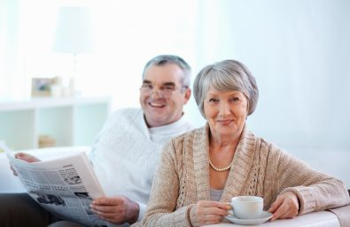 Portrait of happy senior woman and her husband at home