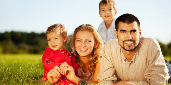 Happy family of 4 people lying ona grass under summer sun. Focus is on the man.