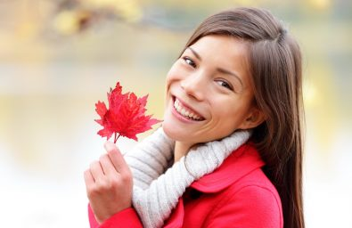 Fall girl holding red Autumn leave outside. Asian woman outdoor portrait in red seasonal autumn coat by fall forest lake. Female model smiling happy looking at camera. Mixed race Asian Caucasian girl.