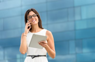 Business woman holding tablet pc computer and calling on cell phone outside corporate building. Caucasian hispanic female executive doing her job using digital communication technology.