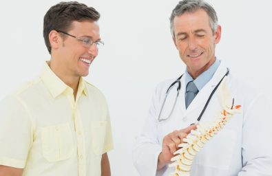 Smiling male doctor showing patient something on skeleton model over white background